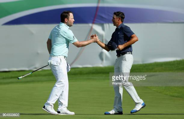 Branden Grace of South Africa and Chase Koepka of the USA shake hands on the 18th green during the third round of the BMW South African Open...