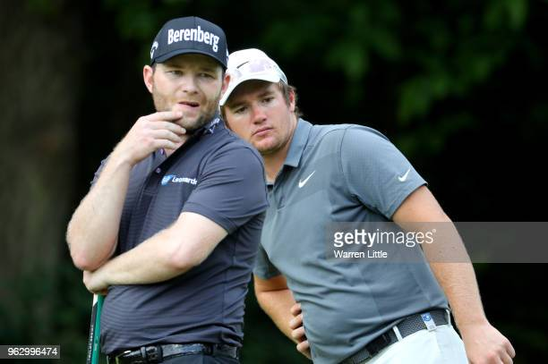Branden Grace of South Africa and Sam Horsfield of England watch a putt during day four and the final round of the BMW PGA Championship at Wentworth...