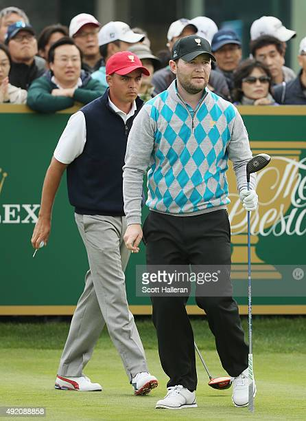 Branden Grace of South Africa and the International Team watches his tee shot on the 16th tee as Rickie Fowler of the United States team looks on...