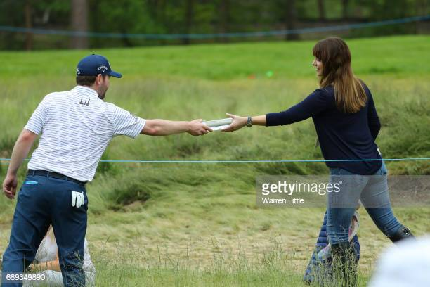 Branden Grace of South Africa hands a water bottle to his partner Nieke Coetzee during the final round on day four of the BMW PGA Championship at...