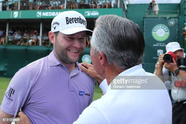 Branden Grace of South Africa is congratulated by Gary Player after his victory on the 18th green during the final round of the Nedbank Golf...