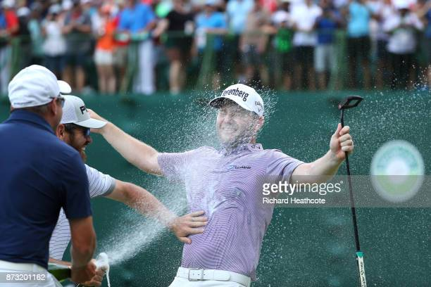 Branden Grace of South Africa is sprayed with champagne after his victory on the 18th green during the final round of the Nedbank Golf Challenge at...