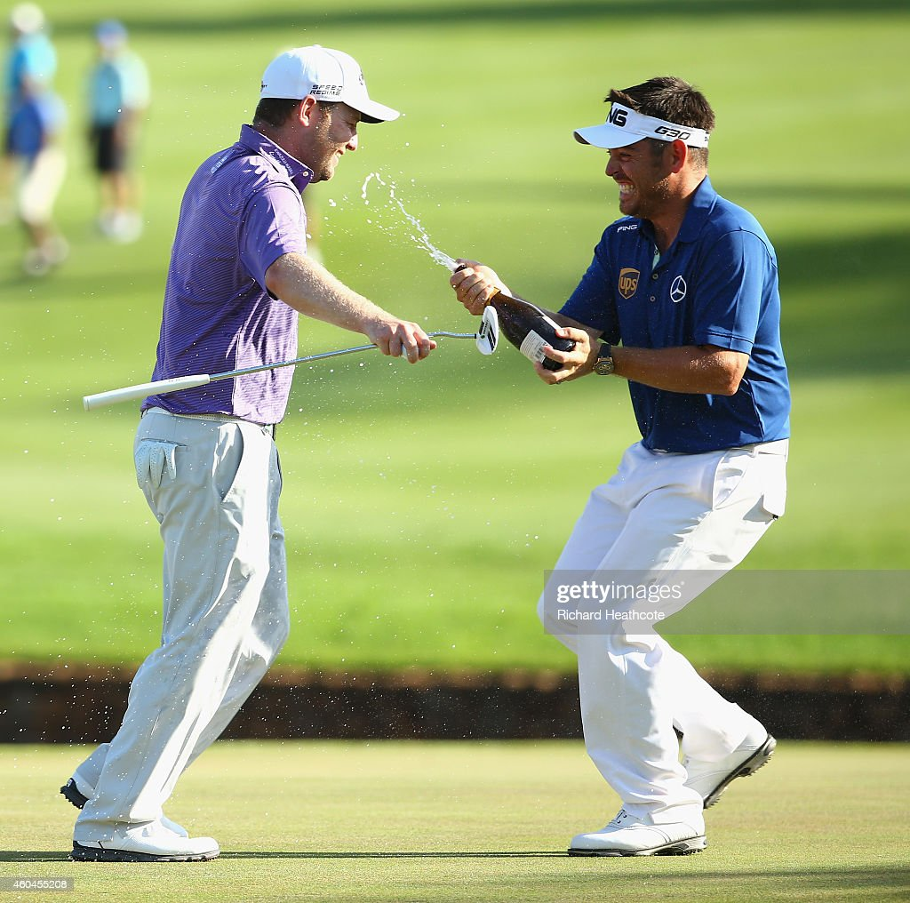 Branden Grace of South Africa is sprayed with champagne by Louis Oosthuizen of South Africa after securing victory in the final round of the Alfred Dunhill Championship at Leopard Creek Country Golf Club on December 14, 2014 in Malelane, South Africa.