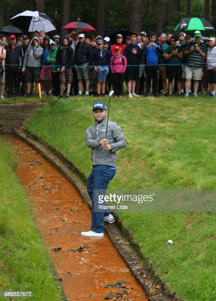 Branden Grace of South Africa plays his second shot from a ditch on the 12th hole during the final round on day four of the BMW PGA Championship at...