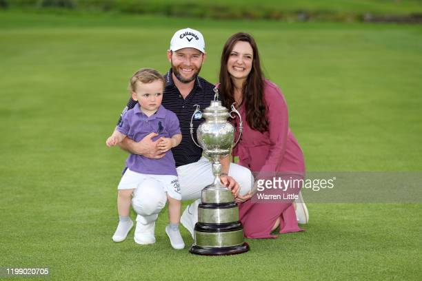 Branden Grace of South Africa poses for a photograph with the trophy with wife Nieke and Son Roger after winning the tournament during Day Four of...