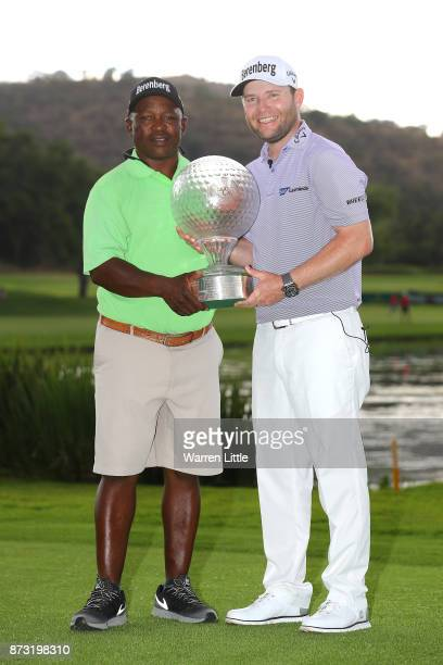 Branden Grace of South Africa poses with caddie Zak Rasego and the trophy after his victory during the final round of the Nedbank Golf Challenge at...