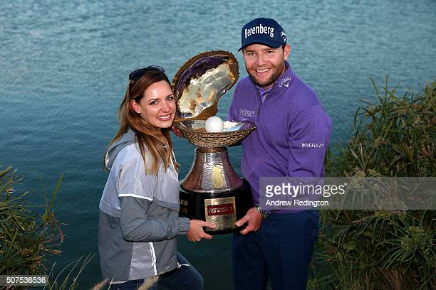 Branden Grace of South Africa poses with the Mother of Pearl trophy and his girlfriend Nieke Coetzee following his victory in the Commercial Bank...