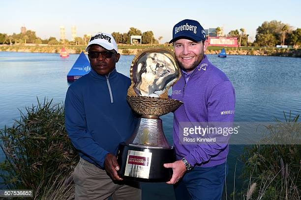 Branden Grace of South Africa poses with the Mother of Pearl trophy and his caddie Zack Rasego following his victory in the Commercial Bank Qatar...