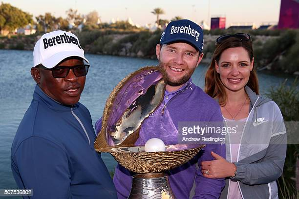 Branden Grace of South Africa poses with the Mother of Pearl trophy his girlfriend Nieke Coetzee and caddie Zack Rasego following his victory in the...