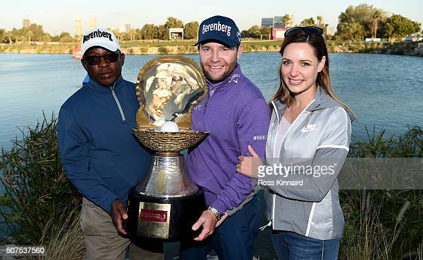 Branden Grace of South Africa poses with the Mother of Pearl trophy and his caddie Zacharia Rasego and girlfriend Nieke Coetzee following his victory...