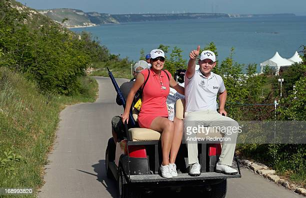 Branden Grace of South Africa rides on a buggy with his girlfriend Nieke Coetzee after winning his quarterfinal match on Day Three of the Volvo World...