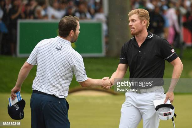 Branden Grace of South Africa shakes hands with Andrew Dodt of Australia during day four of the BMW PGA Championship at Wentworth on May 28 2017 in...