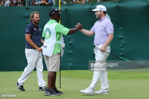 Branden Grace of South Africa shakes hands with caddie Zak Rasego on the 18th green after his victory during the final round of the Nedbank Golf...