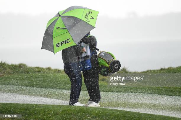 Branden Grace of South Africa takes cover under an umbrella during a hail storm during the final round of the ATT Pebble Beach ProAm at Pebble Beach...