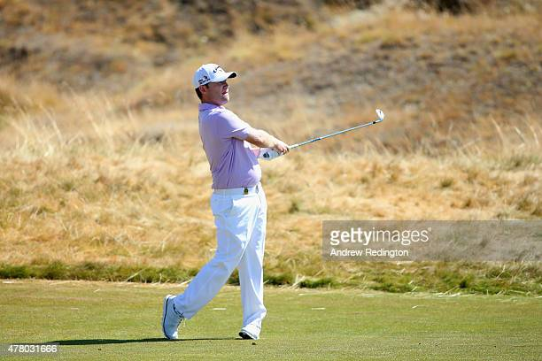 Branden Grace of South Africa watches his second shot on the fifth hole during the final round of the 115th US Open Championship at Chambers Bay on...