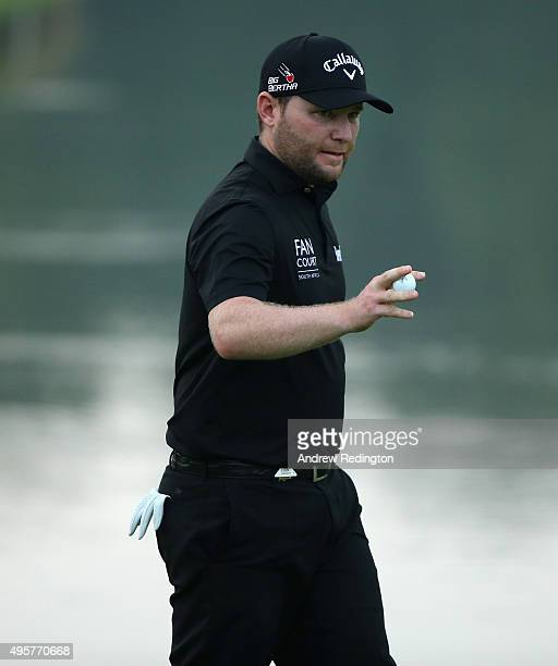 Branden Grace of South Africa waves to the crowd after his birdie on the ninth hole during the first round of the WGC HSBC Champions at the Sheshan...