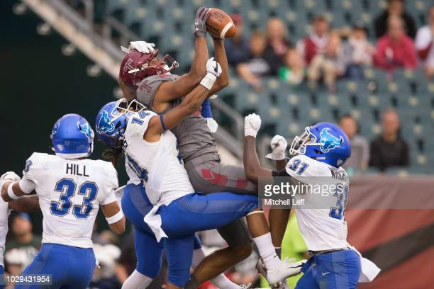 Branden Mack of the Temple Owls catches a touchdown pass against Tyrone Hill Brandon Williams and Kadofi Wright of the Buffalo Bulls as time expired...