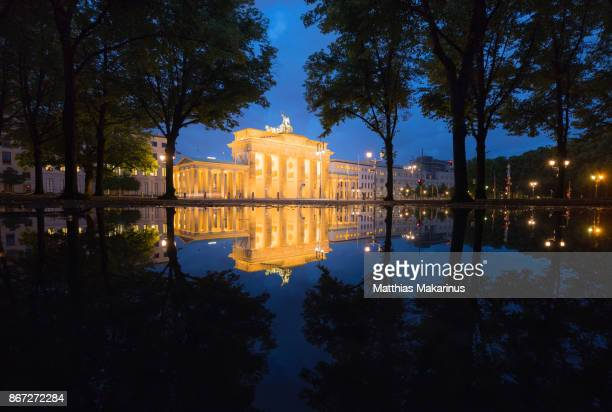 brandenburg gate berlin illuminated panorama with blue sky and city reflection - makarinus stock photos and pictures