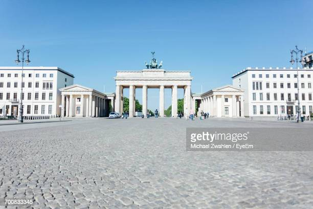 Brandenburg Gate By Street In City Against Blue Sky