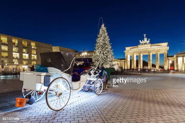 Brandenburg Gate with christmas tree and horse coach (Berlin, Germany)