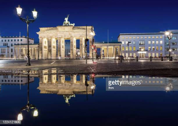 brandenburger tor (brandenburg gate) with reflection in a puddle at blue hour (berlin, germany) - porta cittadina foto e immagini stock