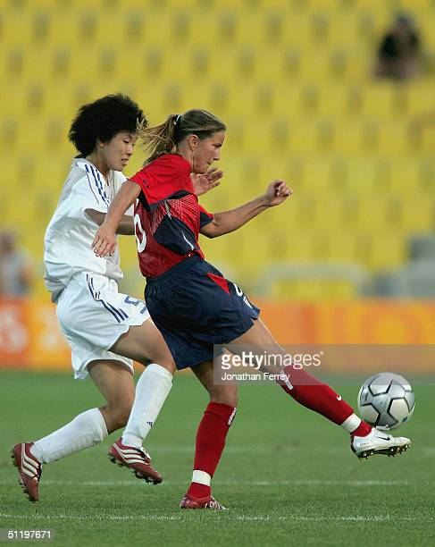 Brandi Chastain of the United States kicks the ball away from Eriko Arakawa of Japan in the women's football quarterfinal match on August 20 2004...