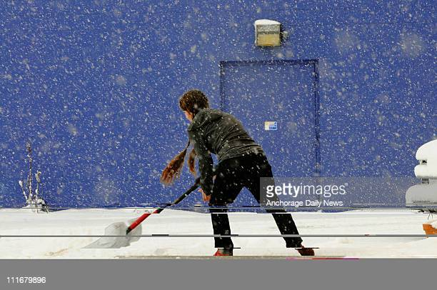 Brandi Mayfield shovels outside Blaine's Art store in midtown Anchorage, Alaska, Tuesday, April 5, 2011. A spring snowstorm left a few inches of snow...