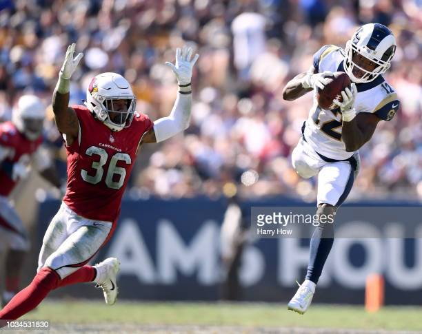 Brandin Cooks of the Los Angeles Rams makes a jumping catch for a first down in front of Budda Baker of the Arizona Cardinals during the fourth...