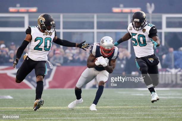 Brandin Cooks of the New England Patriots is defended by Jalen Ramsey and Telvin Smith of the Jacksonville Jaguars in the first quarter during the...