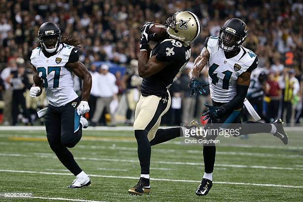Brandin Cooks of the New Orleans Saints catches a pass for a touchdown in front of Nick Marshall and Johnathan Cyprien of the Jacksonville Jaguars...