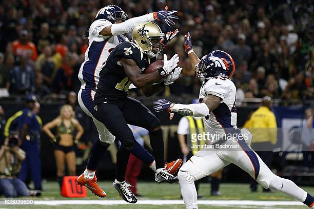 Brandin Cooks of the New Orleans Saints catches a touchdown over TJ Ward of the Denver Broncos and Bradley Roby during the second half of a game at...