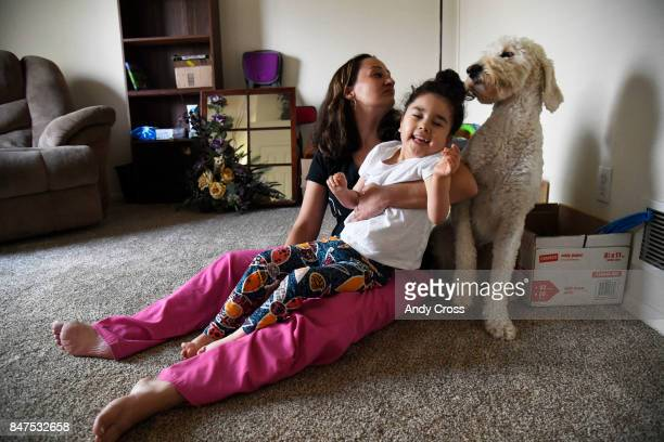 Brandis Perry holds her daughter Chloe who has epilepsy as their service dog Trusty the 2yearold Golden Doodle from Noelle's Dogs Four Hope stands...
