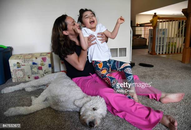 Brandis Perry holds her daughter Chloe who has epilepsy as their service dog Trusty the 2yearold Golden Doodle from Noelle's Dogs Four Hope lays next...