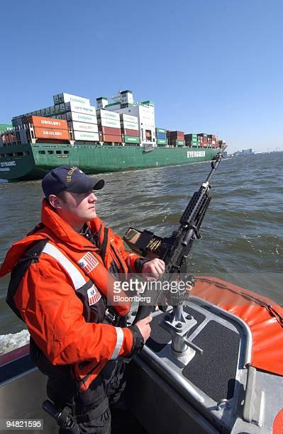 Brandon Achey Coast Guard machine technician third class stands in the bow of a Coast Guard boat patrolling the port of Hampton Roads near Norfolk...
