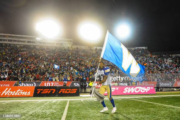 Brandon Alexander of the Winnipeg Blue Bombers runs with his team's flag after winning the 107th Grey Cup Championship Game against the Hamilton...