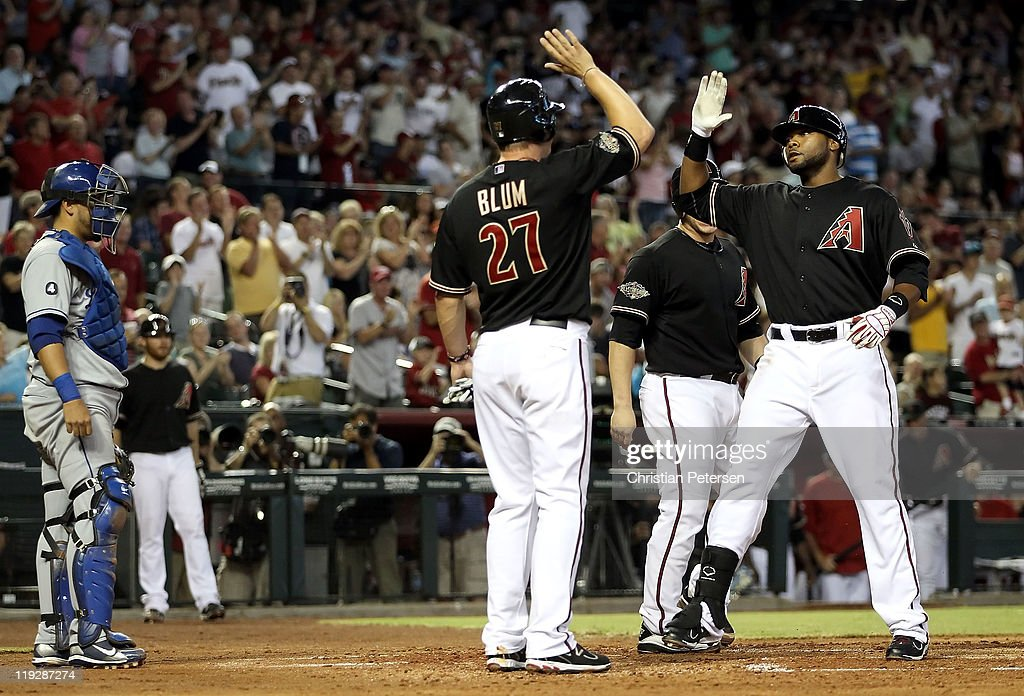 Brandon Allen #29 of the Arizona Diamondbacks high-fives teammates Geoff Blum #27 and Miguel Montero #26 after Allen hit a three-run home run against the Los Angeles Dodgers during the second inning of the Major League Baseball game at Chase Field on July 16, 2011 in Phoenix, Arizona.