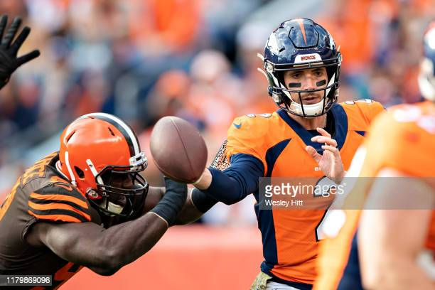 Brandon Allen of the Denver Broncos throws a pass while being hit by Devaroe Lawrence of the Cleveland Browns at Broncos Stadium at Mile High on...
