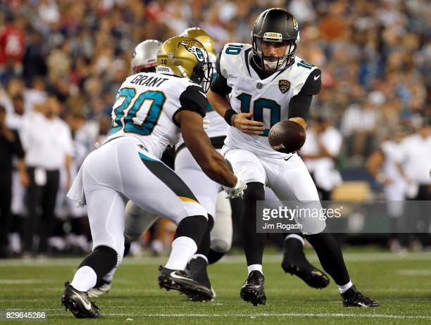 Brandon Allen of the Jacksonville hands the ball to Corey Grant who scored a touchdown on the play against the New England Patriots in the second...