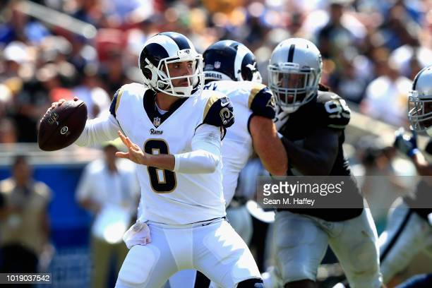 Brandon Allen of the Los Angeles Rams looks to pass as Fadol Brown of the Oakland Raiders defends during the second half of a preseason game at Los...