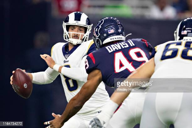 Brandon Allen of the Los Angeles Rams tries to avoid the rush of Jamal Davis II of the Houston Texans during week four of the preseason at NRG...