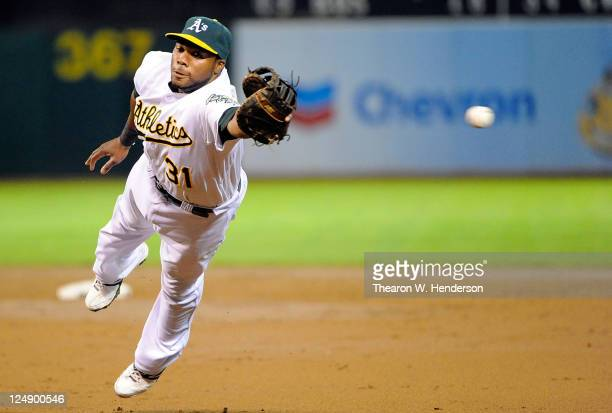Brandon Allen of the Oakland Athletics dives but can't catch this ball that goes for a double off the bat of Erick Aybar of the Los Angeles Angels of...