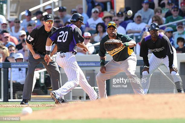 Brandon Allen of the Oakland Athletics waits for a throw at first base as Wilin Rosario of the Colorado Rockies hustles back to the bag at Salt River...