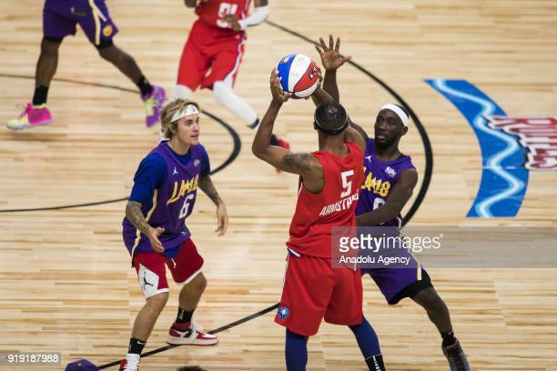Brandon Armstrong of Team Clippers is guarded by Nate Robinson and Justin Bieber of Team Lakers during the 2018 NBA AllStar Celebrity Game as part of...