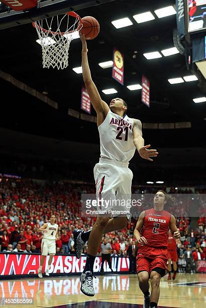 Brandon Ashley of the Arizona Wildcats lays up a shot past Dusty Hannahs of the Texas Tech Red Raiders during the first half of the college...