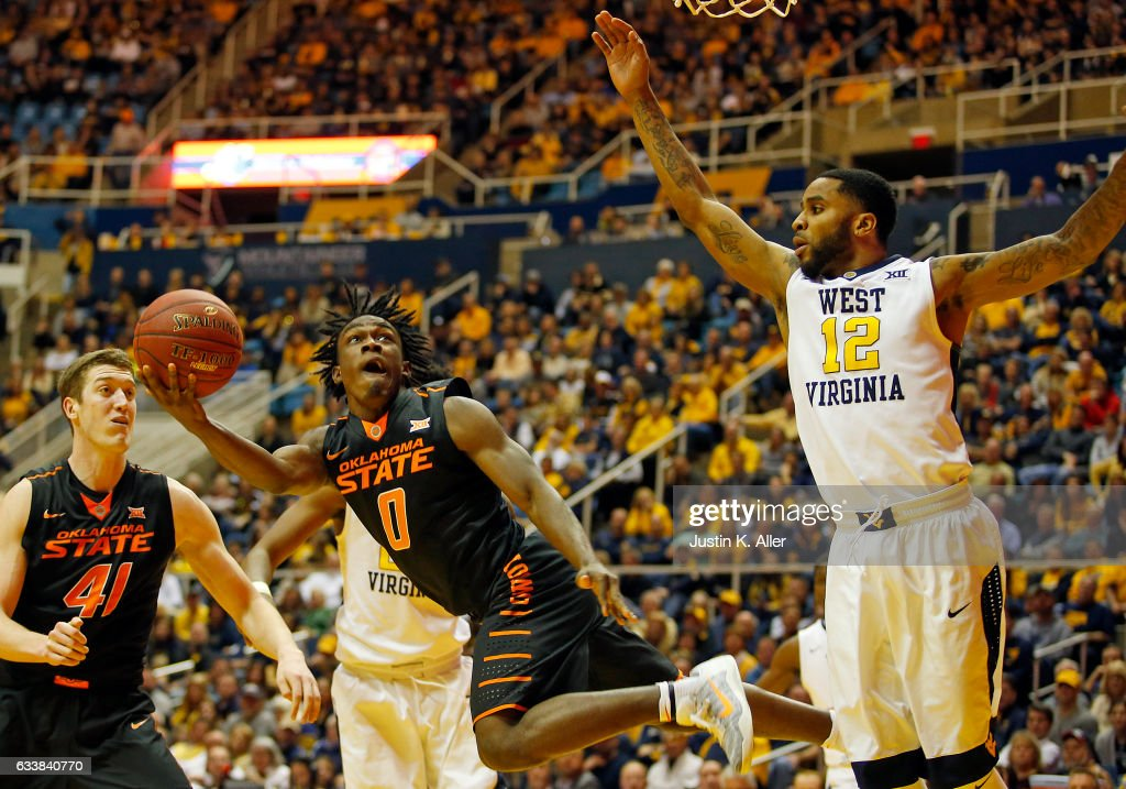 Brandon Averette #0 of the Oklahoma State Cowboys is fouled taking the ball to the hoop against Brandon Watkins #20 and Tarik Phillip #12 of the West Virginia Mountaineers at the WVU Coliseum on February 4, 2017 in Morgantown, West Virginia.