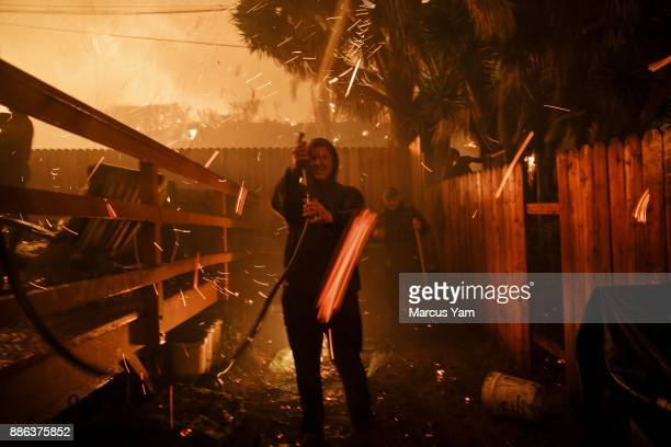 Brandon Baker center and Prescott McKenzie right take cover from the flying embers during a brush fire on December 5 2017 in Ventura California