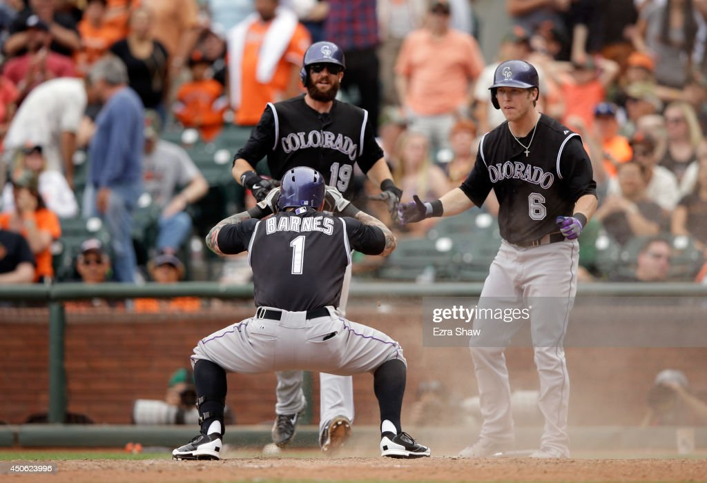 Brandon Barnes #1 of the Colorado Rockies celebrates with Charlie Blackmon #19 and Corey Dickerson #6 after he hit an inside-the-park home run in the ninth inning of their game against the San Francisco Giants at AT&T Park on June 14, 2014 in San Francisco, California.