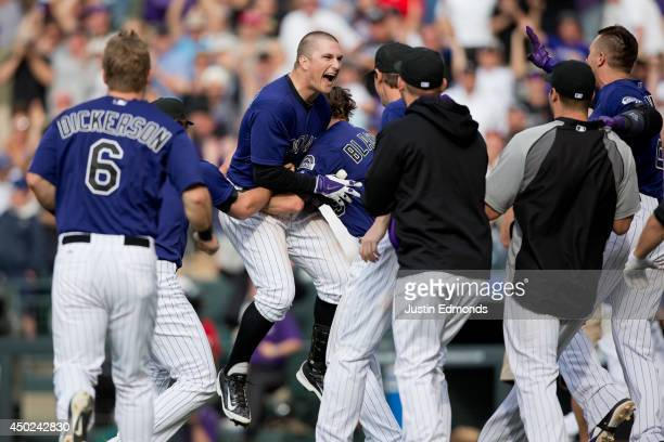 Brandon Barnes of the Colorado Rockies is mobbed by teammates after his game winning RBI triple in the 10th inning to defeat the Los Angeles Dodgers...