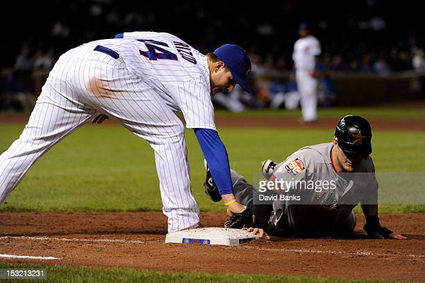 Brandon Barnes of the Houston Astros dives back safely into first base as Anthony Rizzo of the Chicago Cubs makes a tag in the eighth inning on...