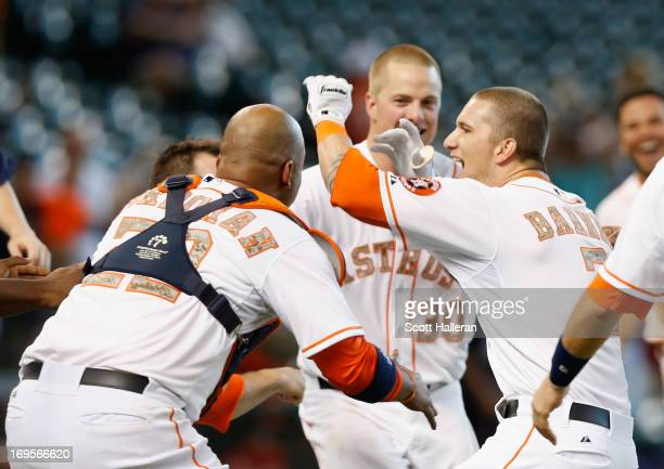 Brandon Barnes of the Houston Astros is mobbed by his teammates after his RBI double in the 12th inning to defeat the Colorado Rockies 32 at Minute...
